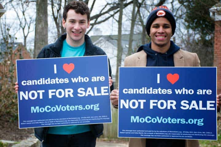 """young men holding signs that say """"I love candidates who are not for sale"""""""